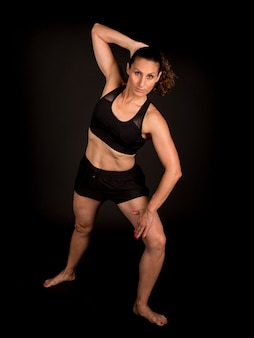 Женщина делает гимнастику на черном фоне