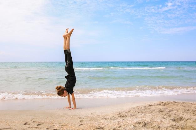 Женщина делает гимнастику на пляже