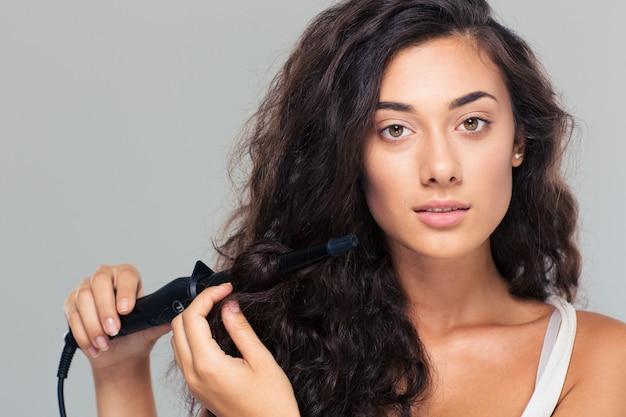 ストレートヘアアイロンでヘアスタイルをしている女性