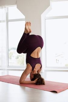 Женщина делает стойку на коврик для йоги. день йоги