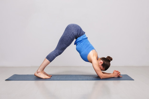 Woman doing hatha yoga asana ardha pincha mayurasana