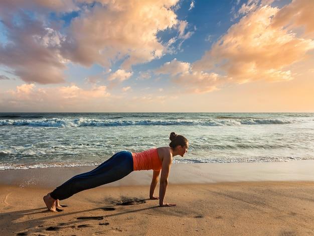 Woman doing hatha yoga asana plank pose outdoors