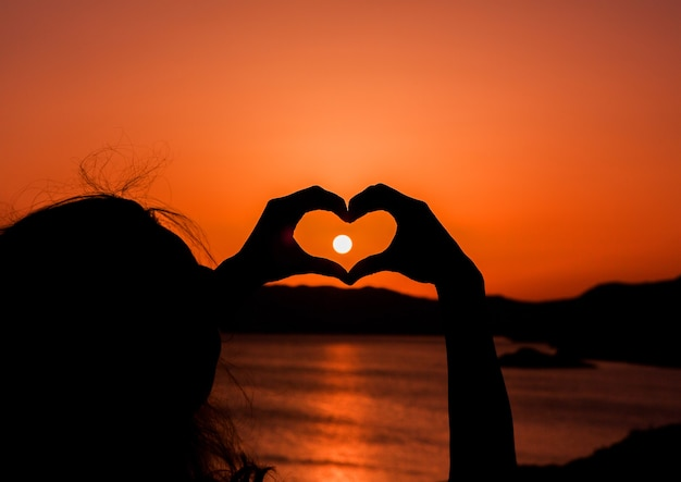 Woman doing heart gesture with hand over the sun at sunshine