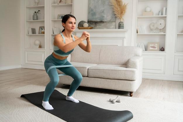 Женщина делает свою тренировку дома на фитнес-коврике