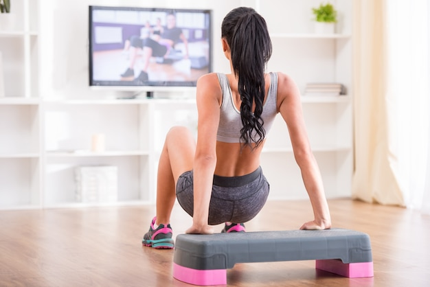 Woman doing home exercises while watching program.