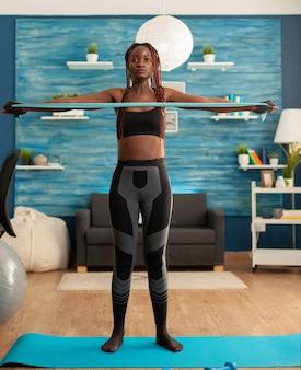 背中の筋肉のためのヨガマットに輪ゴムでリビングルームでホームトレーニングをしている女性