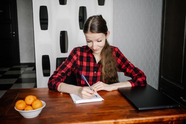 家で宿題をしている女性