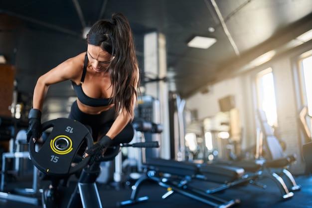 Женщина делает упражнения по гиперэкстензии в тренажерном зале