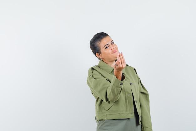 재킷, 티셔츠에 이탈리아 제스처를 하 고 쾌활한 찾고 여자.
