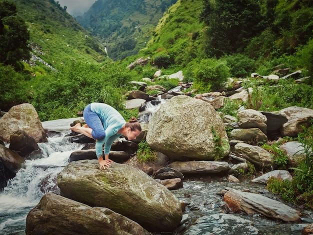 Женщина делает kakasana асана руку баланса у водопада