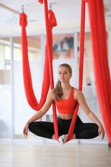 Woman doing leg muscles stretching with red ribbons