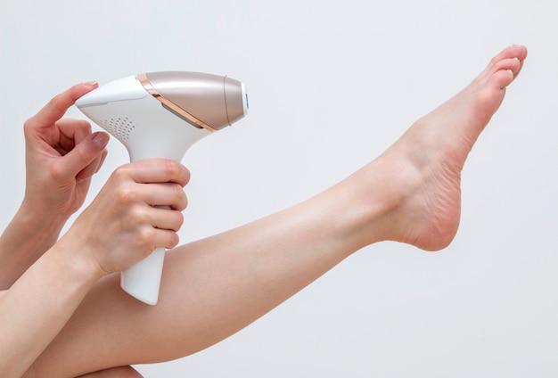 Женщина делает процедуру фотоэпиляции ног дома