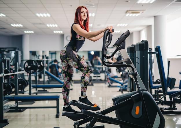 Женщина делает упражнения ног на машине степперов, в тренажерном зале