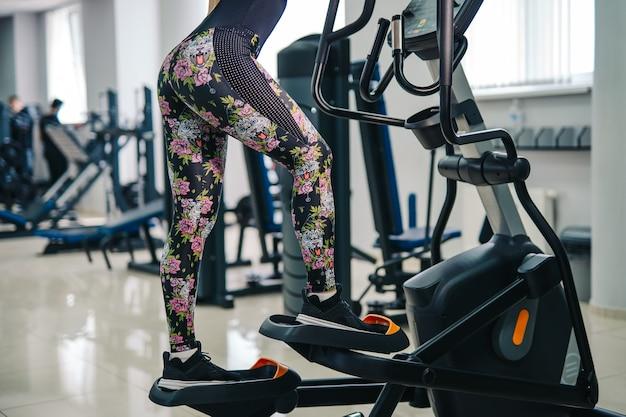 체육관에서 계단 스테퍼 기계에 다리 운동을하는 여자 프리미엄 사진
