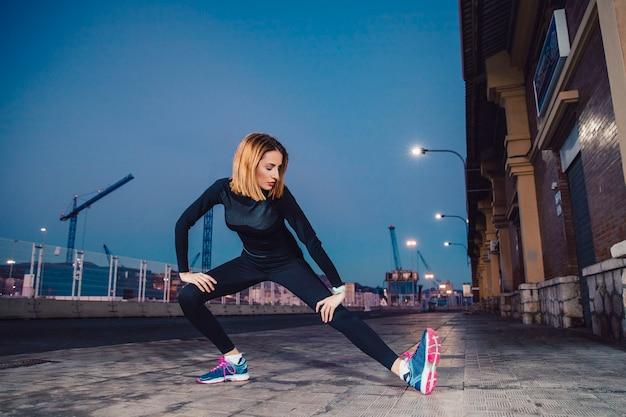 La donna che fa le gambe si esercita sulla via