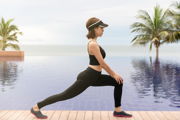 Woman doing low lunge exercise on the beach with sunrise on the morning.