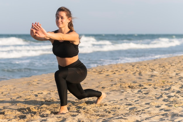 Woman doing lunges on the beach