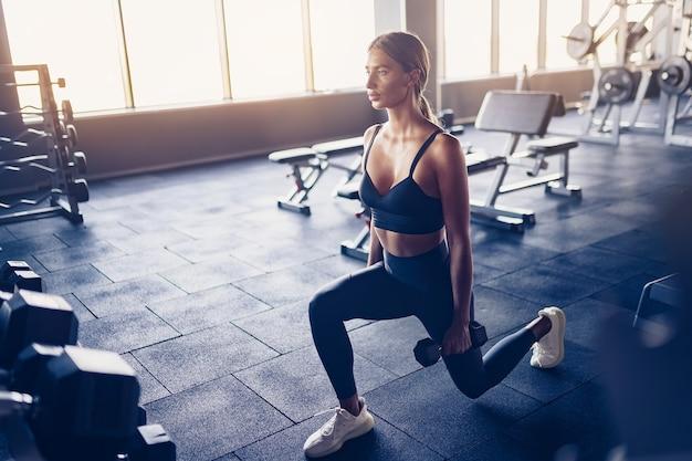 여자 체육관에서 아령으로 돌진 운동을 하 고 있습니다.