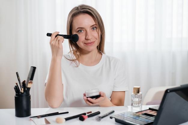 自宅でメイクをしている女性、装飾的な化粧品を適用します