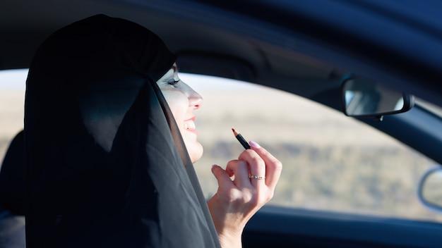 Женщина делает макияж в машине, опаздывая на работу.,