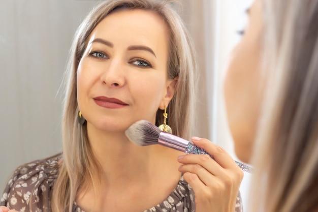 Женщина делает макияж перед зеркалом