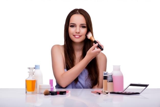Woman doing makeup on white