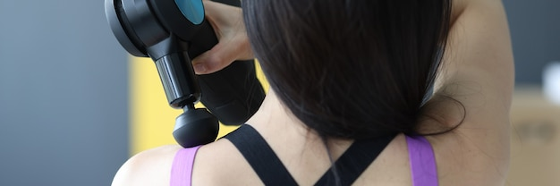 Woman doing massage of muscles of neck and back with percussion massager closeup