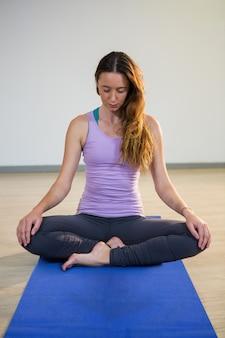 Woman doing meditation on exercise mat