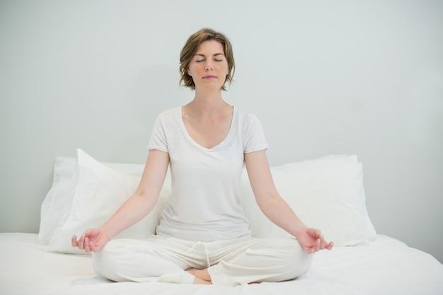 Женщина делает медитацию на кровати в спальне