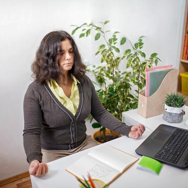 オフィスでストレスを軽減するために瞑想をしている女性