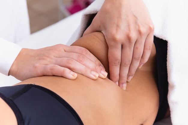 Женщина делает моделирующий массаж в клинике