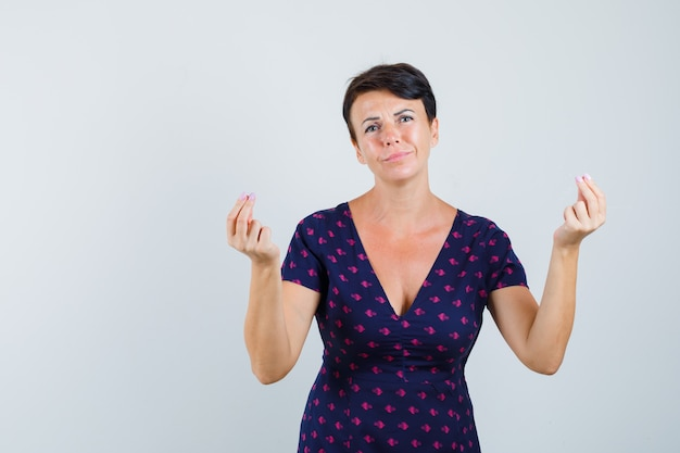 Woman doing money gesture in dress and looking indigent.