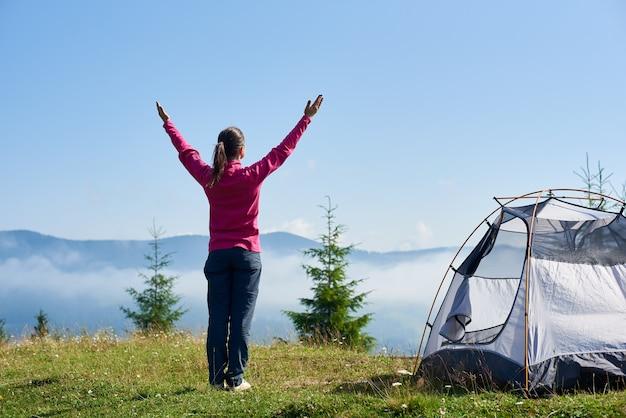 テントの近くで朝の運動をしている女性