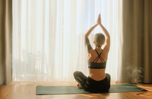 Woman doing morning yoga practice meditation namaste sun salutation at home sitting in lotus pose