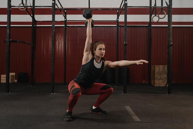 ジムで頭上ダンベルスクワットをしている女性。ウエイトでトレーニングを練習している女性アスリート