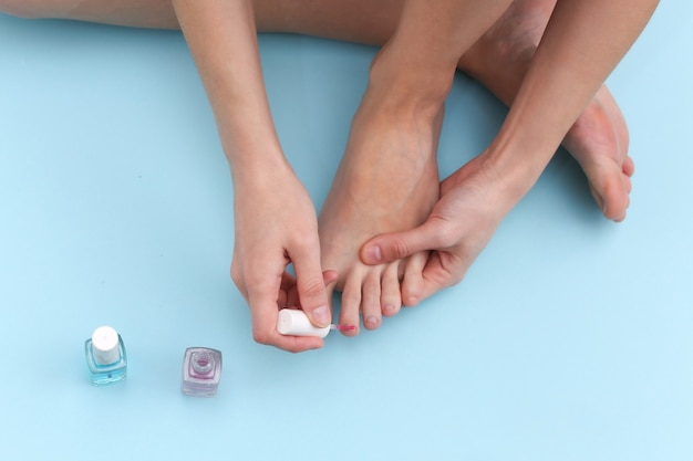 Woman doing pedicure while sitting on blue studio background