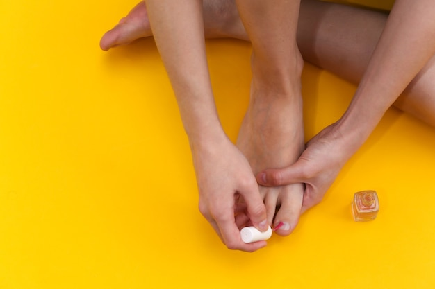 Woman doing pedicure while sitting on yellow studio background