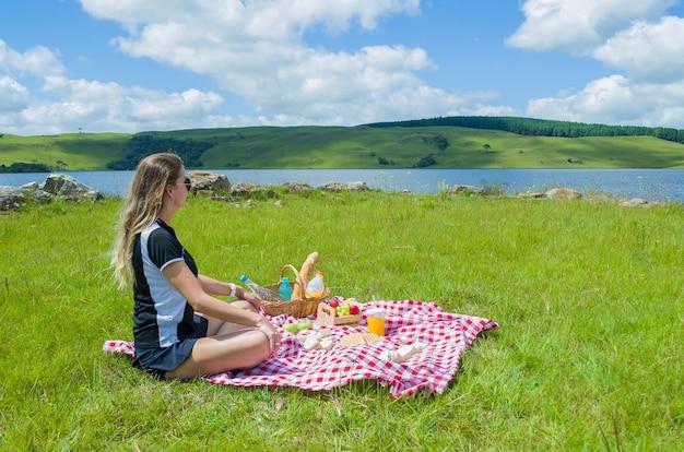 緑の芝生でピクニックをしている女性