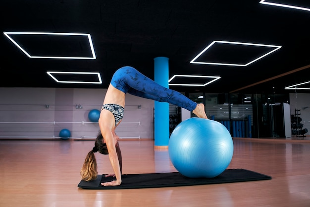 Woman doing pilates exercises on fitness ball in a modern gym. swiss ball.