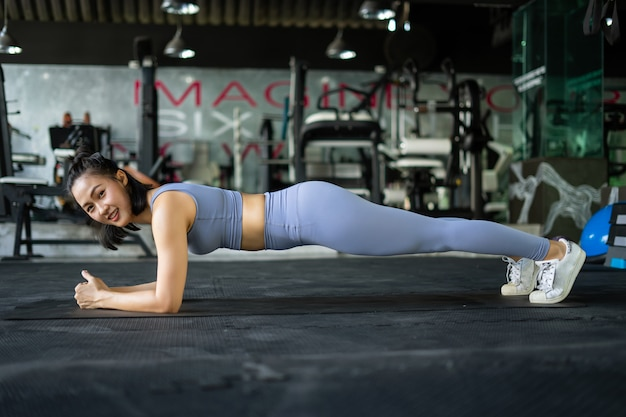 Woman doing plank exercise on mat in gym.
