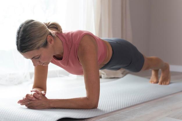 屋内で板のエクササイズをしている女性