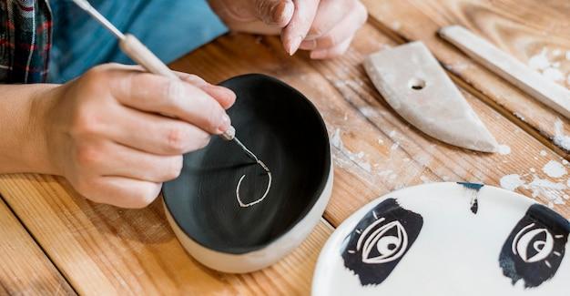 Donna che fa un capolavoro di ceramica nel suo laboratorio
