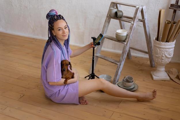 Donna che fotografa un prodotto con il suo cane