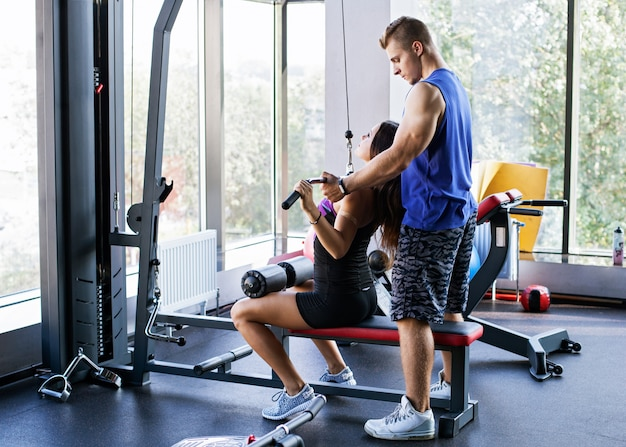 Woman doing pull down exercise for the back under a personal trainer's