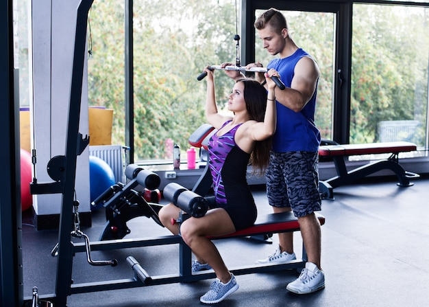 Woman doing pull down exercise under a personal trainer's