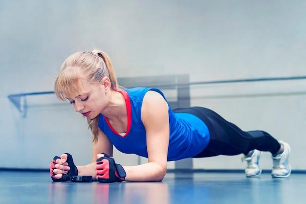 팔굽혀펴기 운동을 하는 여자. 크로스핏 운동을 하는 강한 여성. 금발은 그녀의 팔꿈치에 서서 바닥에 있는 초시계를 본다. 지구력 운동.