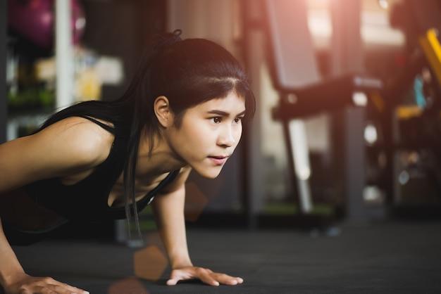 ジムでプッシュアップをやっている女性。プッシュアップをしている筋肉の女性。運動のコンセプト。