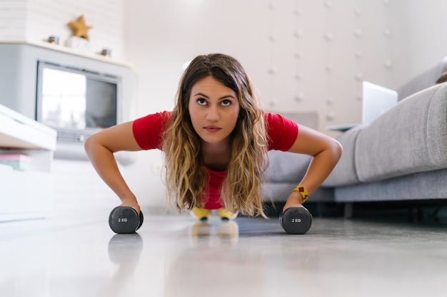 Woman doing push ups with dumbbells at home