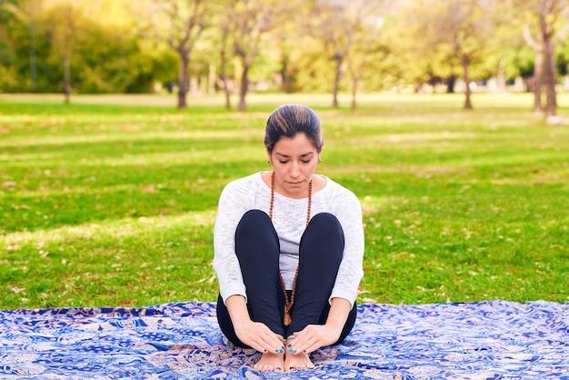 公園のチャクラポーズでレイキとヨガのポーズをしている女性