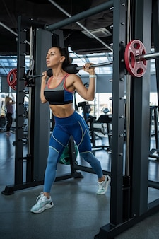 Woman doing reverse lunges on smith machine at gym
